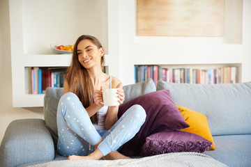 Young woman sitting on sofa and enjoying her morning coffee at home