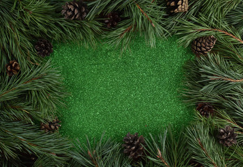 Green glitter background surrounded with pine branches and pinecones. Christmas background