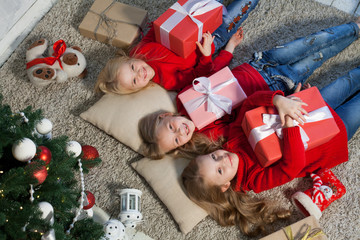 two small girls blondes lie near a Christmas tree gifts new year holiday