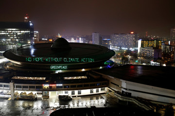 Greenpeace environmental activists project words 'No hope without climate action' on the roof of the venue of the COP24 UN Climate Change Conference 2018 in Katowice