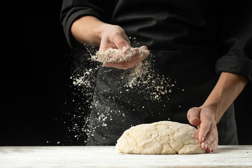 Cook baker prepares bread, focaccia, pizza, buns, sweets. Horizontal photo. Bakery concept, cooking flour products. Design for text.