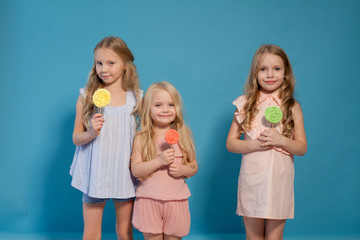 three beautiful young girls and sweet candy lollipops