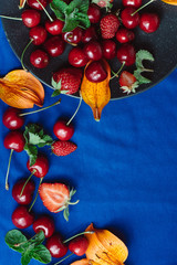 Ripe, fresh sweet cherry and berries in black plate on blue  background.  Healthy diet. Top view, copy space. Place for text.