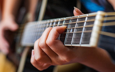 Closeup of young woman hand playing on black acoustic guitar