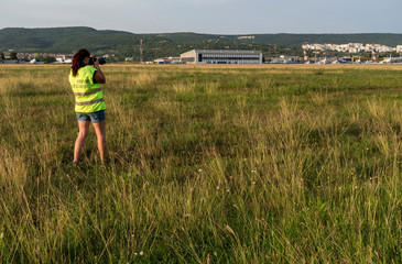 A photographer takes photos of take-off and landing planes.