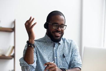 Black millennial cheerful student learn foreign language via internet using computer and headphones...