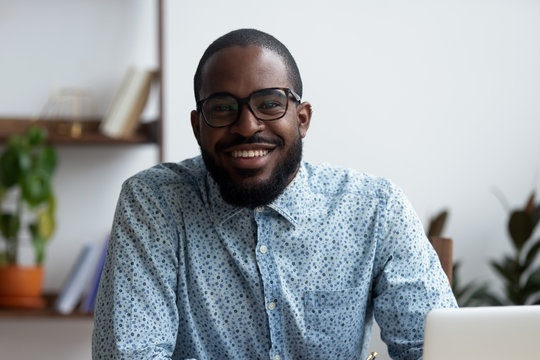 Head shot portrait of positive african american businessman in eyeglasses sitting at office desk using laptop. Confident happy with guileless smile entrepreneur looking at camera posing in workplace