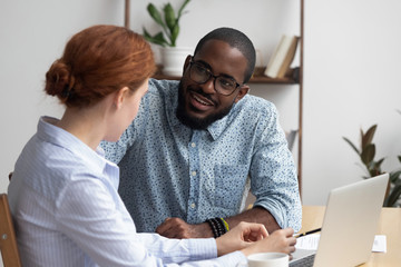 Diverse workmates take break during workday talking have pleasant conversation feels amity interest to each other. Multiracial businesspeople negotiating in relaxed atmosphere solve business issues