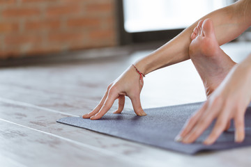 Close-up of feet and hands of attractive sporty young woman practicing yoga indoor on wooden floor...