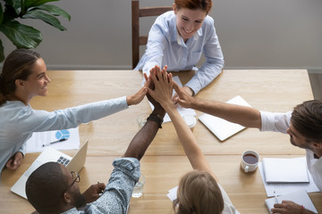 Diverse millennial partners company staff feels happy reached business goal giving high five stack palms together sitting at office desk in boardroom in conference, top above view. Team spirit concept