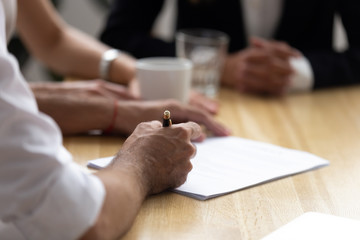 Involved parties sitting at desk in boardroom after successful negotiations businessman signing contract, close up focus on man hands hold pen ready affirm agreement paper making selling buying deal