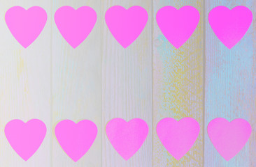 frame of paper pink hearts on wooden retro grunge background with copy space, top view flat lay
