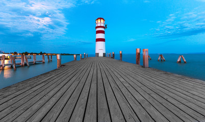 Morning view of lighthouse tower and walking wooden path