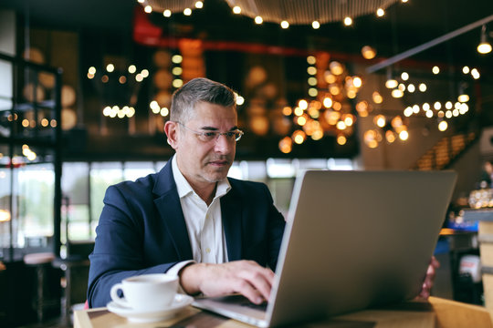Middle-aged businessman with serious face dressed smart casual sitting in cafe and using laptop. On table coffee.