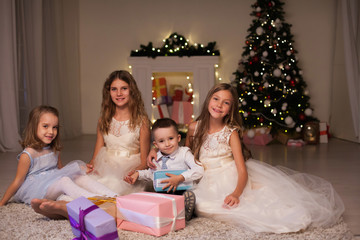 the little boy and three girls kids open Christmas presents new year winter Christmas tree