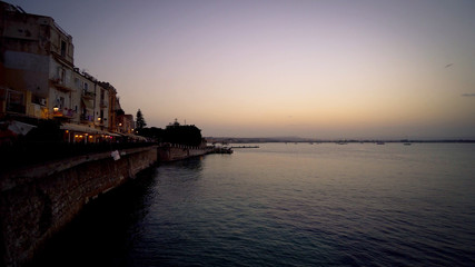 Wall Mural - Sunset over the sea to Sicily, the island of Ortigia.