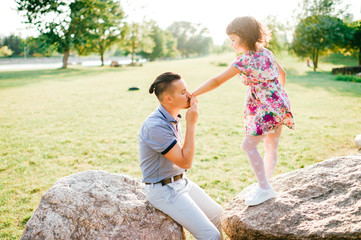Dad and daughter summer outdoor activity. Loving father adore his lovely playful baby. Parent and child have fun in park. Carefree childhood. Happy family lifestyle portrait. Cheerful girl clapping