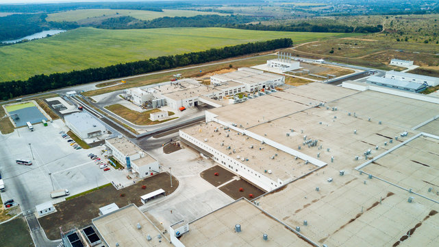 Top view of modern big factory with white buildings. Industrial complex. Aerial view.