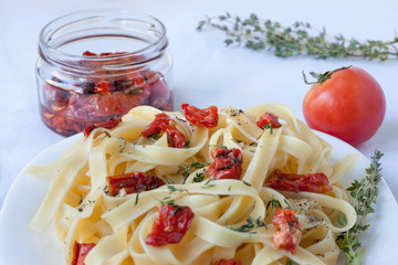 Fettuccine pasta with sun-dried tomatoes and rosemary is lying on a white plate.