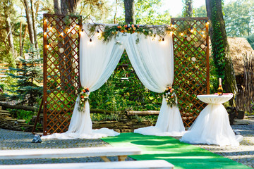 Beautiful place made with wooden square and floral decorations for outside wedding ceremony in wood. Cute wedding arc decorated with flowers and pine branches.
