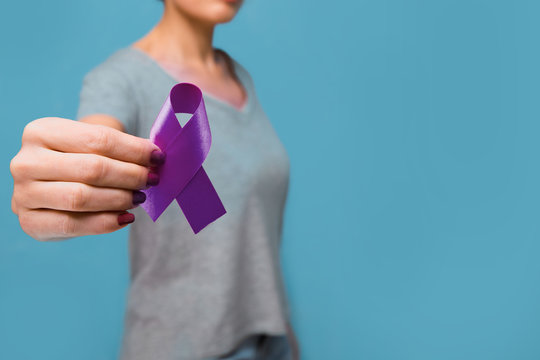 Elderly woman holding purple ribbon awareness w copy space. Symbol is used to raise awareness for Alzheimer's disease, elder abuse, epilepsy, pancreatic cancer, thyroid cancer and lupus. Close up.