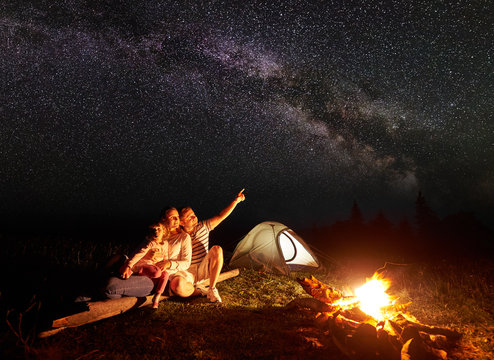 Tourist family camping in mountains at night, sitting on log near illuminated tent and burning bonfire. Mother holding in arms small daughter, father pointing at bright stars in dark sky and Milky way