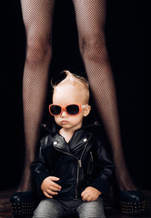 Rock it. Adorable little music fan. Small boy at female legs. Rock style child. Little rock star. Small child boy in sunglasses and rocker jacket. Rock and roll fashion trend. Music for children