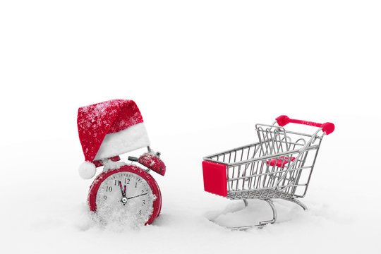 Shopping cart and alarm clock on the snow. Last minutes of christmas sale. Countdown to the end of discounts. Hurry up for gifts. Preparing for the holiday. Special offers. Have time to buy.