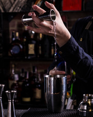 Spoed Foto op Canvas Bartender making refreshing coctail on a bar background. Dark moody style. Ice in tha glass