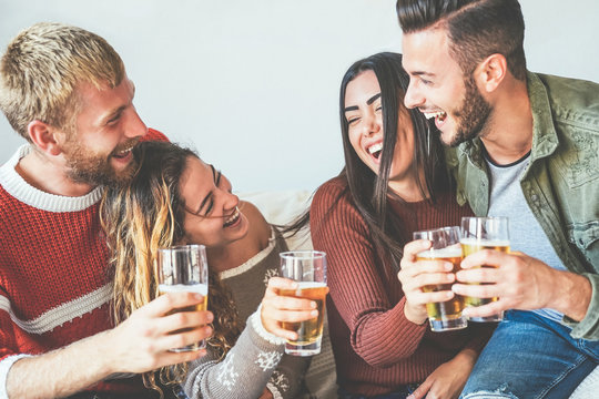 Group of happy friends cheering with beer at home - Millennial Young people having fun drinking and laughing together sitting on sofa - Friendship, entertainment and youth lifestyle holidays
