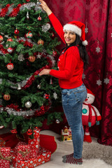 Happy woman arranging the Xmas tree