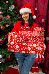 Happy woman holding many Christmas gifts