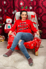 Happy woman sitting on chair with Christmas tree