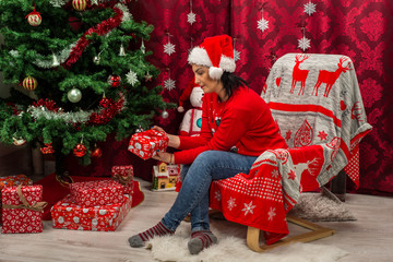 Woman in chair looking at Christmas gift