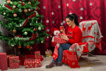 Woman sitting in chair with Xmas gifts