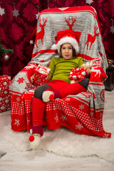 Little boy sitting on chair near Xmas tree
