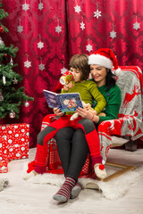 Mother reading Christmas  book to her kid