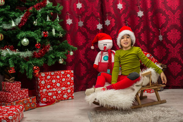Little boy with Santa hat sitting in a sleigh