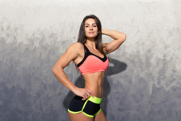 A girl in a pink sports top and black shorts posing on a gray background. Girl instructor at the gym