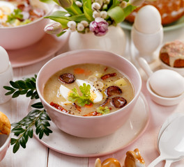 The sour soup (Żurek), polish Easter soup with the addition of smoked  sausage and a hard boiled egg in a ceramic bowl. Traditional Easter dish in Poland