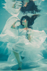 Papiers peints Cygne sexy young bride swimming underwater in white wedding dress, stockings and gloves