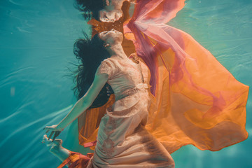 girl with orange dress is dreamy and meditative floating under water, like the soul before reincarnation Fotomurales