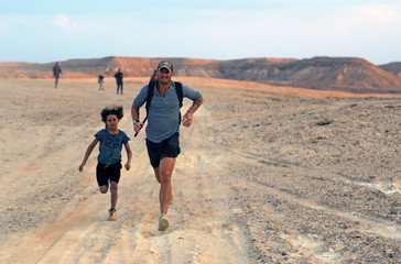 Dutch founder Sytze Boomsma runs with a boy from the group Gouna Mountain Goats after climbing to explore Egypt's undiscovered mountain trails in Wadi Billi, at El-Gouna near the Red Sea