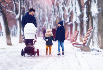happy family, father with kids walking on the winter street