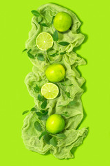 Limes and peppermint on green background