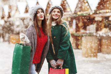 Shopping at Cristmas fair, winter holidays concept: two young beautiful fashionable happy smiling women posing with colorful paper bags in street. City lifestyle. Ladies wearing stylish coats, hats