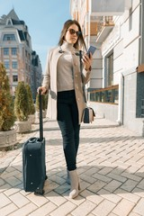 Portrait of traveling young woman with mobile phone and suitcase, fashionable girl on the city street, wearing warm coat, sunny autumn day