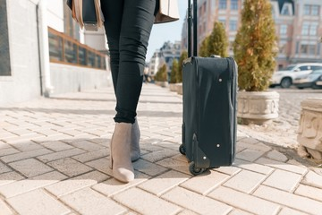 Tourist black suitcase and womans legs on a city street