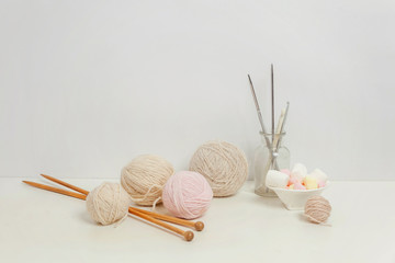Needlework crocheting and knitting club creative workspace. Needlewoman white table cozy workplace with woolen yarn, knitting needles. Working at home women leisure hobby handmade concept. Copy space