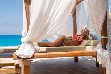 Beautiful young woman lying in a cabana on vacation